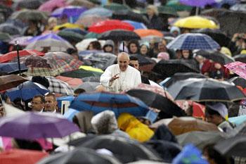 Papa Francesco in Piazza San Pietro tra i fedeli, sotto la pioggia è l'unico senza ombrello