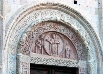 La lunetta sopra il portale della cattedrale di San Rufino rappresenta l'iconografia più antica del santo