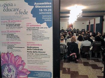 In primo piano il manifesto con il programma dell'assemblea diocesana, sullo sfondo i partecipanti
