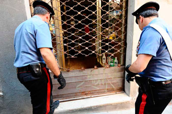 Carabinieri davanti ad una saracinesca tranciata dai  ladri