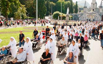 Nella foto alcuni malati a Lourdes. L'11 febbraio, Giornata del malato, è anche la ricorrenza della prima apparizione della Vergine a Bernadette nella grotta di Massabielle