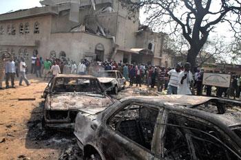 Carcasse di auto bruciate e devastazione dopo lo scoppio di una bomba durante la Messa in una chiesa in Nigeria