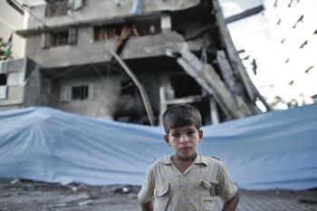 Luglio 2014. Un bambino di Gaza davanti alla sua casa colpita dalle bombe israeliane