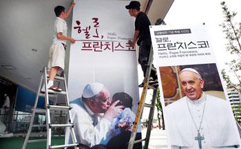 """Allestimento di un poster della mostra fotografica di Papa Francesco """"Ciao, Papa Francesco!"""" presso il Centro Culturale Sejong di Seoul, Corea del sud (Foto AP)"""