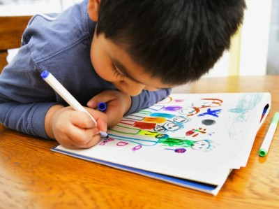 Young boy drawing pictures of his family