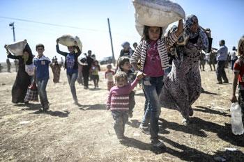 Siriani in fuga dall'Isis trasportano quello che possono diretti verso il confine con la Turchia