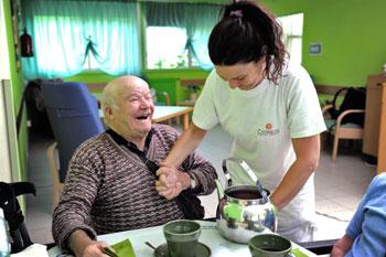 Una volontaria di una cooperativa sociale presta assistenza agli anziani in una casa di cura
