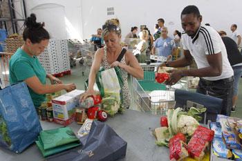 Volontari e operatori in un emporio solidale Caritas