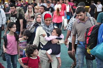 Una donna porta un bambino, insieme a lei altri migranti arrivano nel porto di Pireo vicino ad Atene. (Afp Photo / Louisa Gouliamaki)