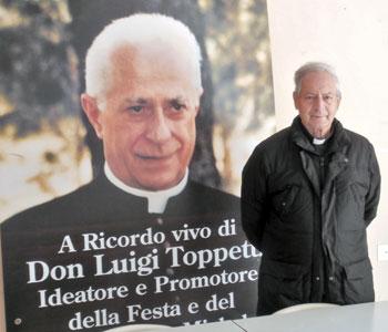 Mons. Girolamo Giovannini accanto ad un manifesto commemorativo di don Luigi Toppetti