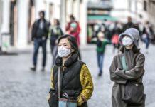 Dopo virus: Due giovani donne asiatiche con la mascherina, per le strade di Roma