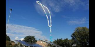 Un rosario fatto di palloncini bianchi e celesti in cielo
