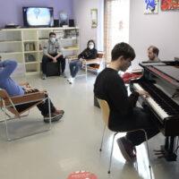 """un ragazzo suona il pèianofortein un'aula del centro """"La Semente"""" di Spello durante un'attività insieme ad altri ragazzi"""