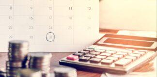 Calcolatrice e soldi su un tavolo, segno di debiti e usura
