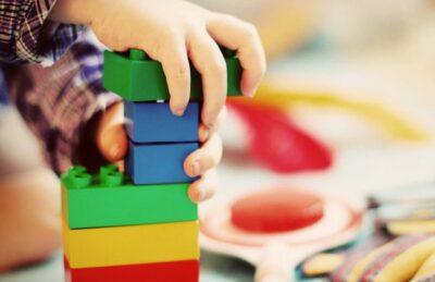 Mani di un bambino giocanocon le costruzioni