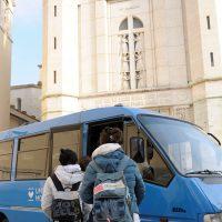 Studenti salgono nel bus scolastico davanti al santuario di Santa Rita